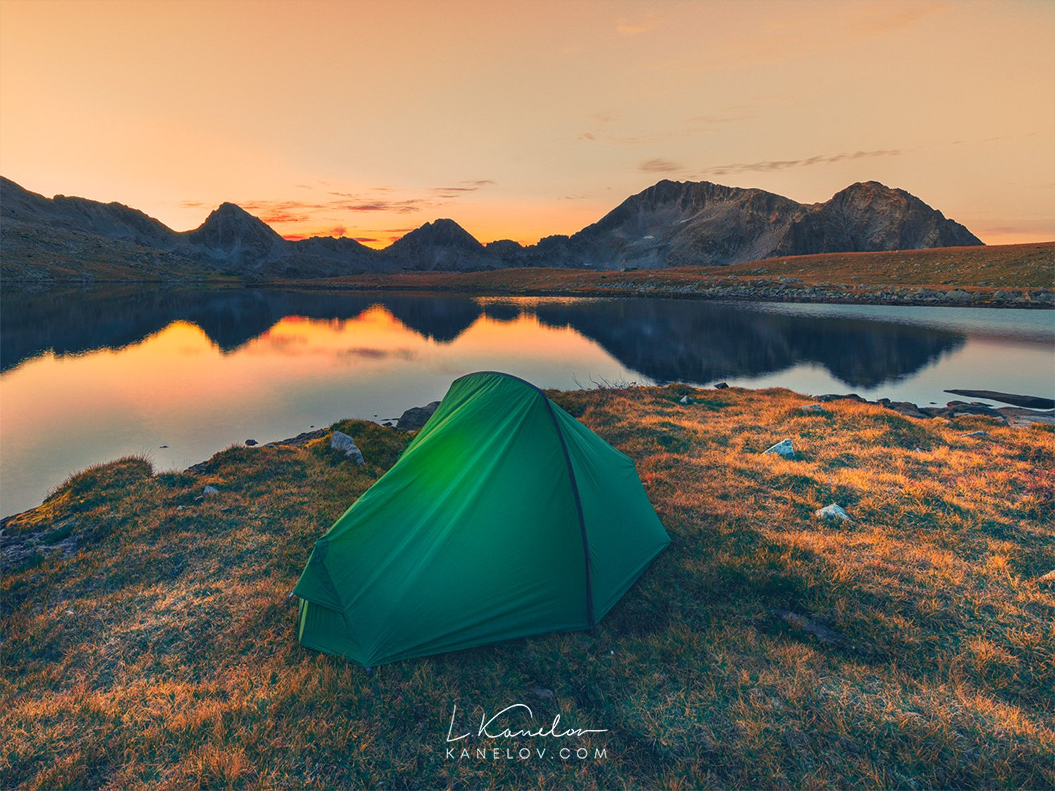 Tent on a mountain lake at sunset